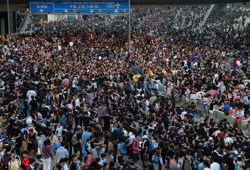 Marea humana. Manifestantes prodemocracia ampliaron sus protestas en todo Hong Kong el lunes, desafiando a los llamamientos para dispersarse en su pulso contra la decisión de Pekín de limitar las reformas democráticas en el centro financiero de Asia.